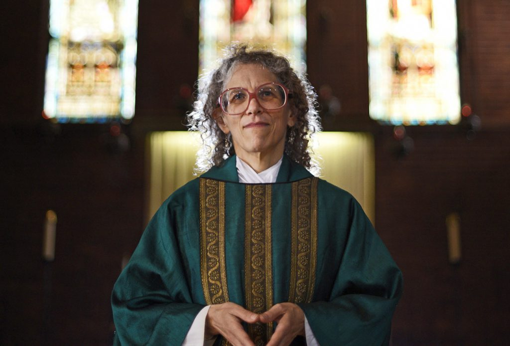 "The Reverend Maggie Helwig, photographed on the chancel steps, wears her full ""eucharistic vestments"" (alb, stole and chasuble) on July 8 2015. Helwig was appointed as priest-in-charge of St.Stephen-In-The-Fields Church in May 2013, and as rector in January 2015 by the Anglican Diocese of Canada. The church is located in downtown Toronto, between the Annex to the north and Kensington Market to the south. Helwig is also a writer and human rights advocate and her writing is on the back burner for the time being since her ministry takes up most of her time."